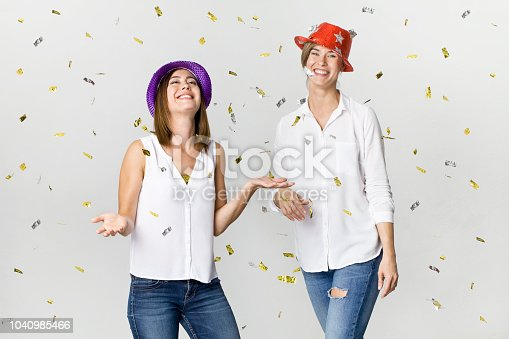 627933752istockphoto Party girlfriends with confetti and colorful hats. It is relaxation and dancing time 1040985466