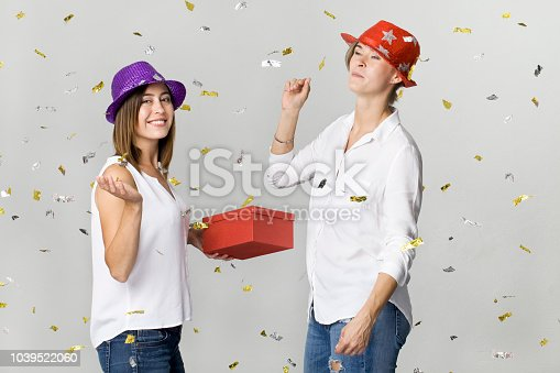 627933752istockphoto Party girlfriends with confetti, gift and colorful hats. It is relaxation and dancing time 1039522060