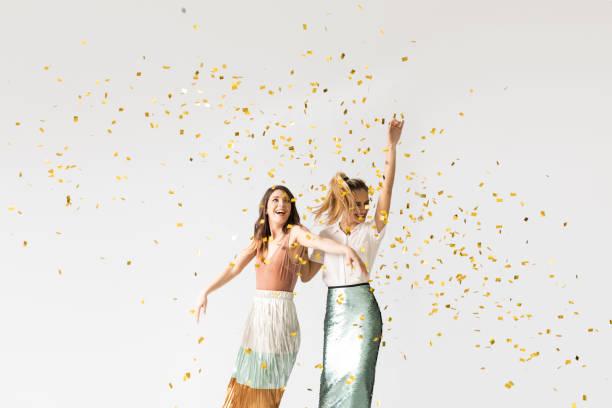 party girls dancing under confetti - женская мода стоковые фото и изображения