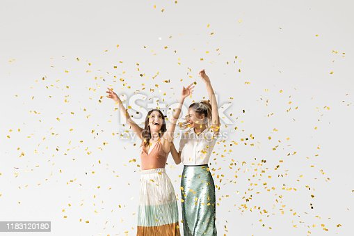 Studio shot of two beautiful stylish young women smiling and dancing under confetti.