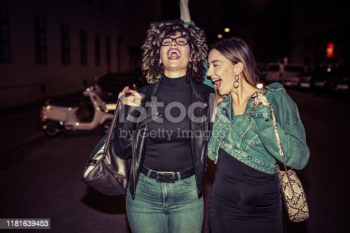 Two young drunk female friends on city street after party