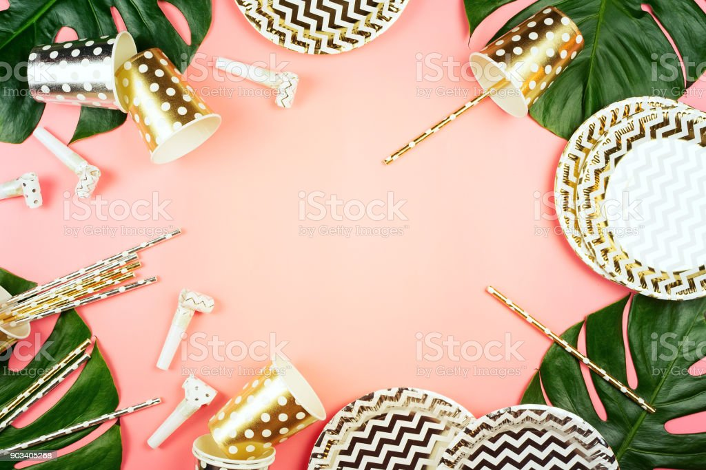 Party golden and silver paper glasses, dishes and straws, party horns and monstera leaves on a table. Pink background. Party concept. stock photo
