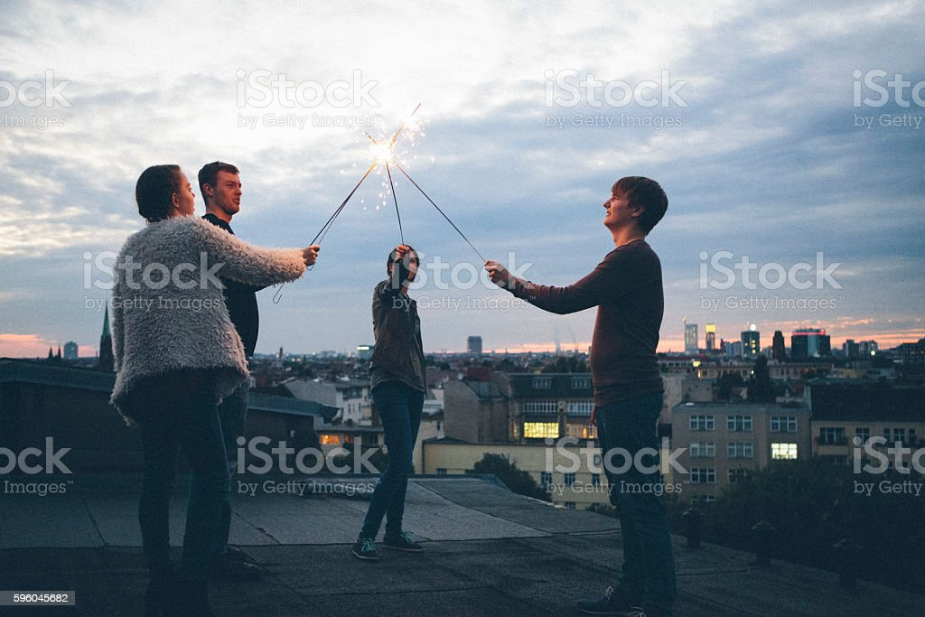 Party: group of young adults standing on roof, holding sparklers stock photo