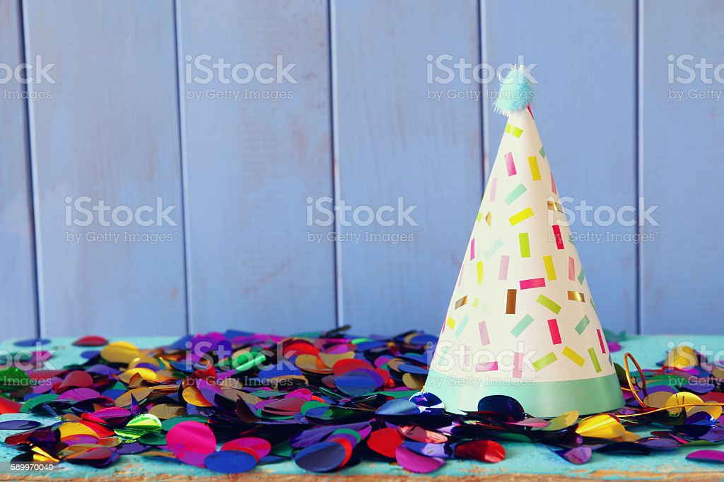 Party hat and colorful confetti on wooden table. ストックフォト