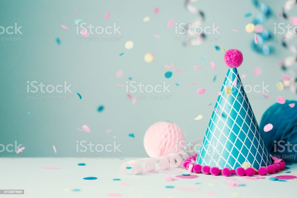 Party hat and falling confetti stock photo