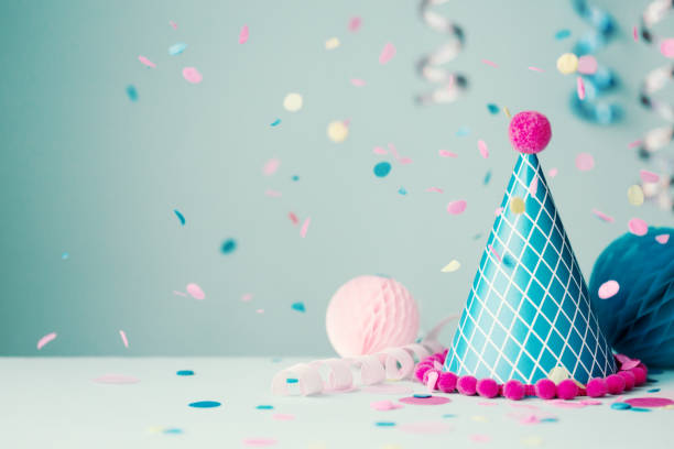 party hat and falling confetti - garland decoration stock photos and pictures