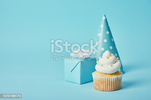 istock party hat, gift box and delicious cupcake on blue background 1070159170