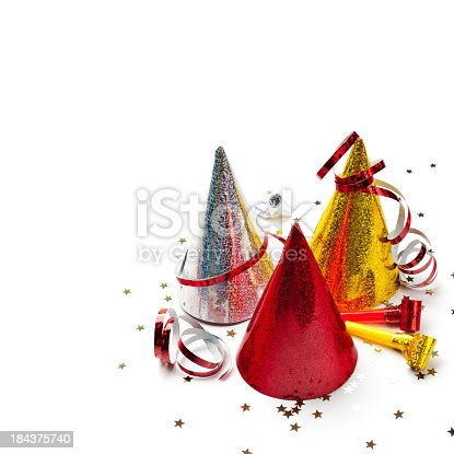 Party decorations: hats, whistles, streamers, confetti on white background. Square composition, copy space, studio shot.