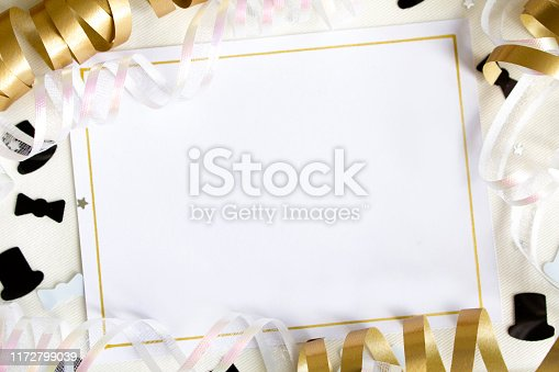 A blank card with white copy space, surrounded with gold ribbons and party confetti.