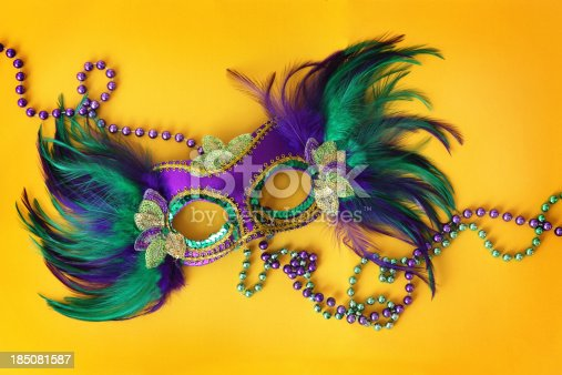 Colorful Mardi Gras mask on a background made with Mardi Gras beads