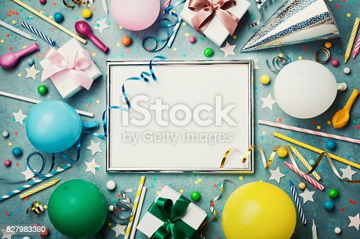 1093222958 istock photo Party or birthday background. Silver frame with colorful balloon, gift box, carnival cap, confetti, candy and streamer. Flat lay. Holiday mockup. 827983360