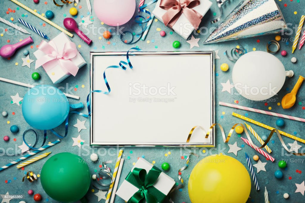 Party or birthday background. Silver frame with colorful balloon, gift box, carnival cap, confetti, candy and streamer. Flat lay. Holiday mockup. stock photo