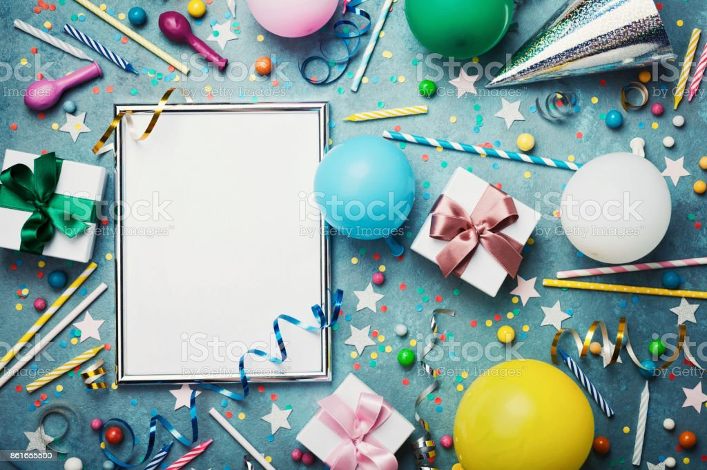 Party or birthday background. Silver frame with colorful balloon, gift box, carnival cap, confetti, candy and streamer. Flat lay. Holiday or festive mockup. stock photo