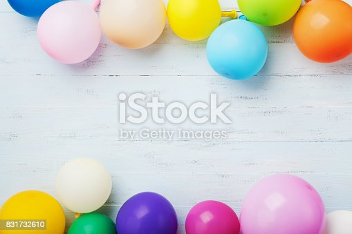 istock Party or birthday banner with colorful balloons on blue wooden background top view. Flat lay. 831732610