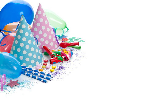 Party or carnival backgrounds. High angle view of multi colored accessories like balloons, party hats, party horn blowers, confetti, candies and streamers shot at the top-left corner of white background leaving useful copy space for text and/or logo. High key DSRL studio photo taken with Canon EOS 5D Mk II and Canon EF 100mm f/2.8L Macro IS USM.