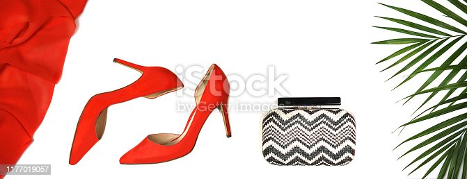 1078252326 istock photo Party outfit: red shoes, accessories clutch, tropical leaves on white background, isolated. 1177019057