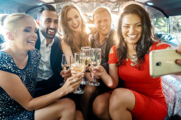Partyvolk in einer Limousine mit Getränken, wobei ein Selbstporträt mit Telefon – Foto