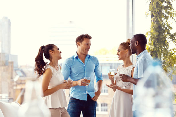 Party Group of friends enjoying their drinks in the livingroom with cityscape in the background.  upper class stock pictures, royalty-free photos & images