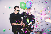 New Year's / Birthday Party. Girl and boy posing in front of white wall with balloons