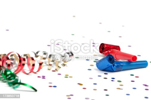 Party ribbon, confetti and horn blower isolated on white.