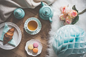 Croissant on the plate, macaroons and tea for breakfast, Flat lay setting of teapot, tea cup, croissant on a plate, macaroons, bouquet of roses and party decor.
