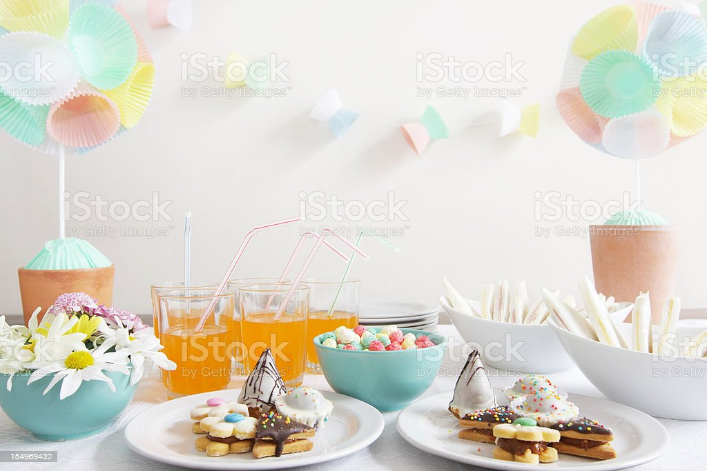 Party table with daisies, cupcake liner topiary and garlands stock photo