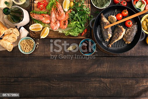 690274036 istock photo Party table with shrimp, fish grilled, salad, different snacks and white wine with border 687679864