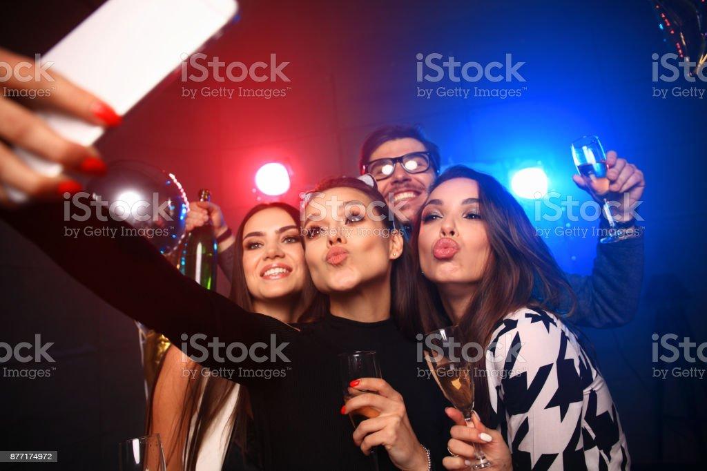 conceito de festa, tecnologia, vida noturna e pessoas - sorrindo amigos com smartphone tomando selfie no clube. - foto de acervo