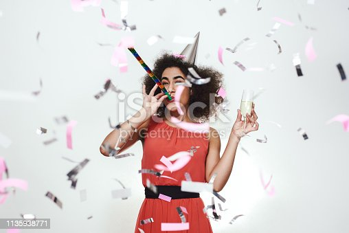 istock Party time! Happy young afro american women in dress and party hat holding a glass with champagne and blowing party whistle with confetti flying around her 1135938771