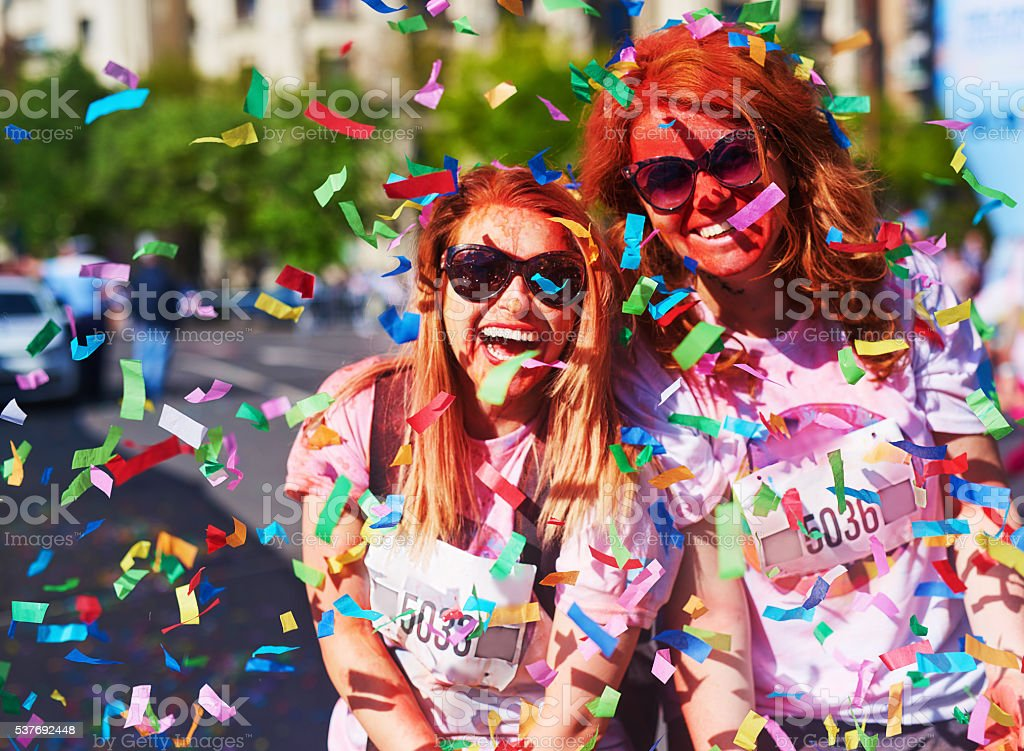 happy two friends in the city laughing and playing with confetti,...