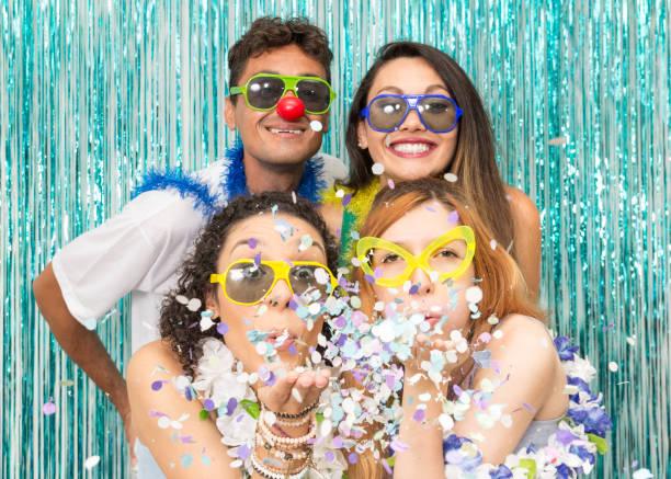 """partygänger feiern karneval in brasilien. mädchen bläst das konfetti aus der handfläche von ihrer hand."""" n - freund kostüme stock-fotos und bilder"""