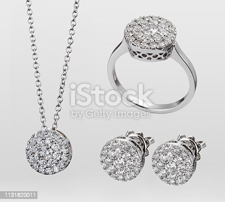 A demi-parure of gemstone jewelry in white gold or silver consisting of three matching pieces - necklace, earrings and ring isolated over a white background