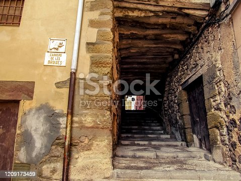 Passage with a staircase on the medieval street of the Witches (Carrero de les Bruixes) in Cervera town (Catalonia, Spain). Ancient tunnel with stone walls and wooden ceiling on a sunny day