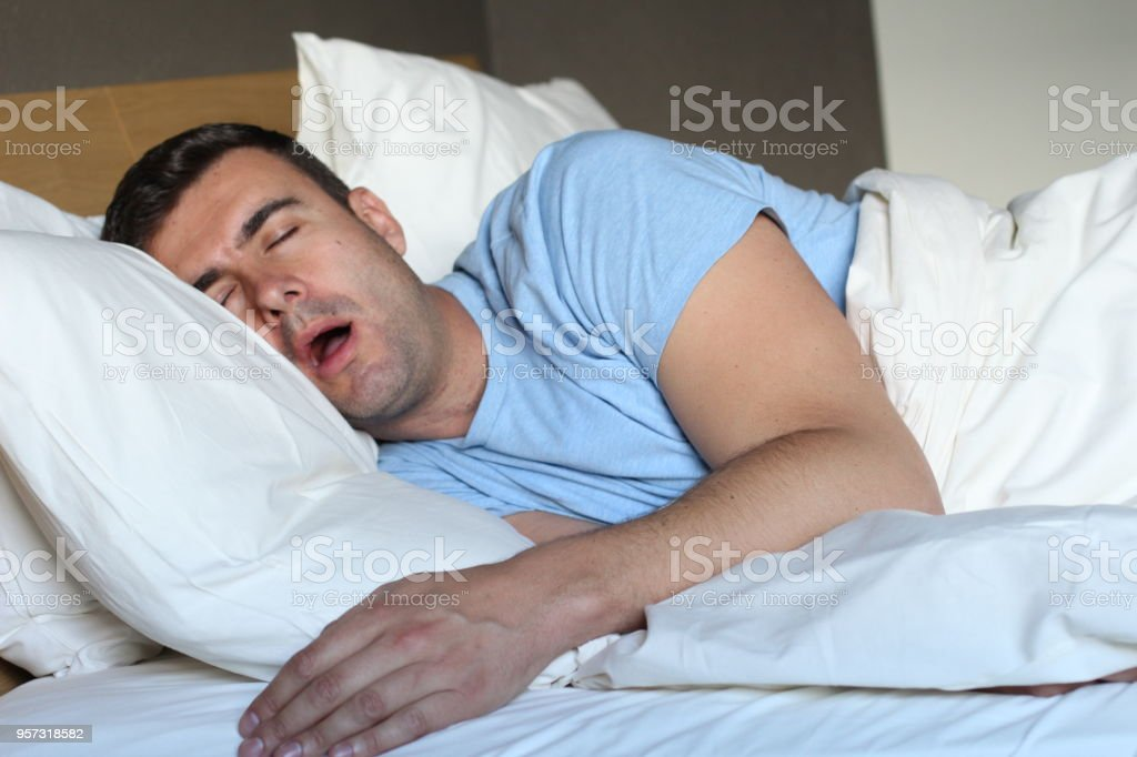 Passed out man drooling in bed stock photo