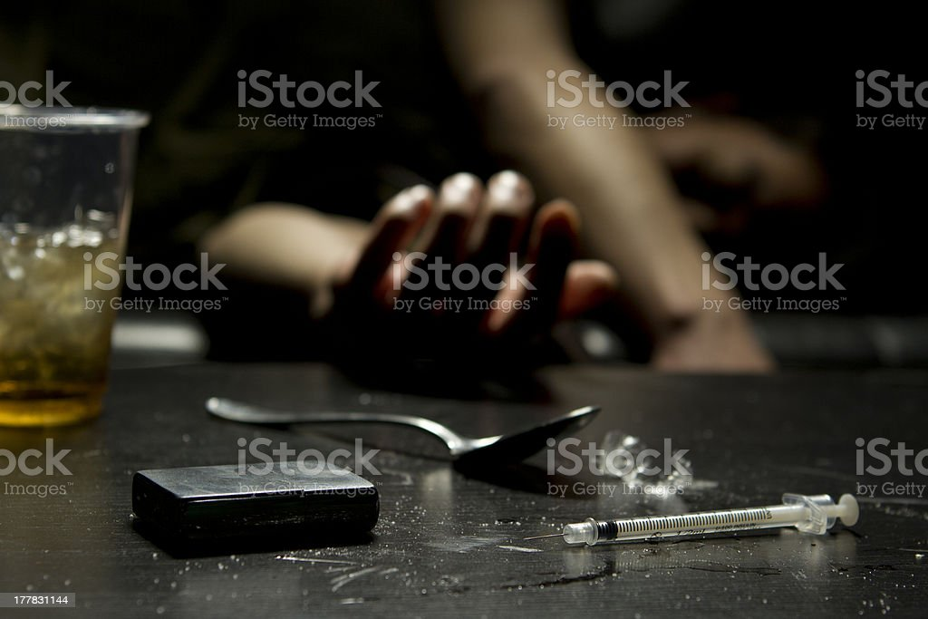 A passed out man on the couch after heroin use stock photo