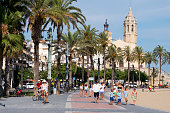 Sitges, Spain - July 27, 2018: People walking by the popular Passeig de la Ribera esplanade in Sitges, Spain, highlighting the Sant Bartomeu i Santa Tecla Church in the background