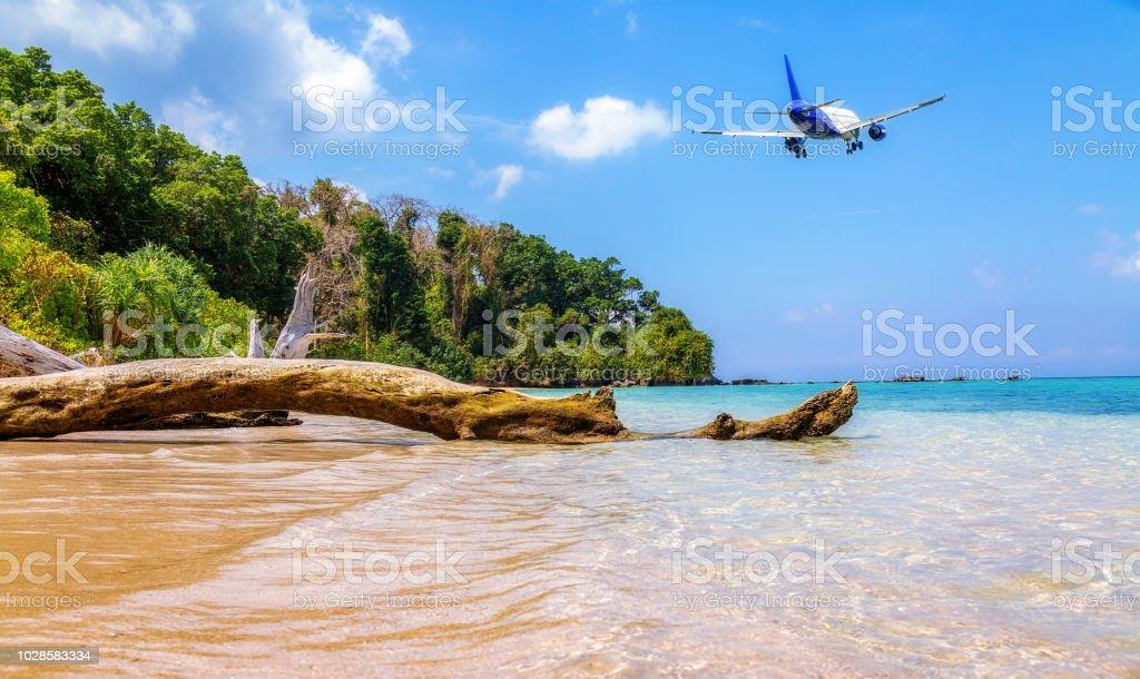 Passenger aircraft flies low over scenic Jolly Bouy island sea beach at Andaman, India. stock photo