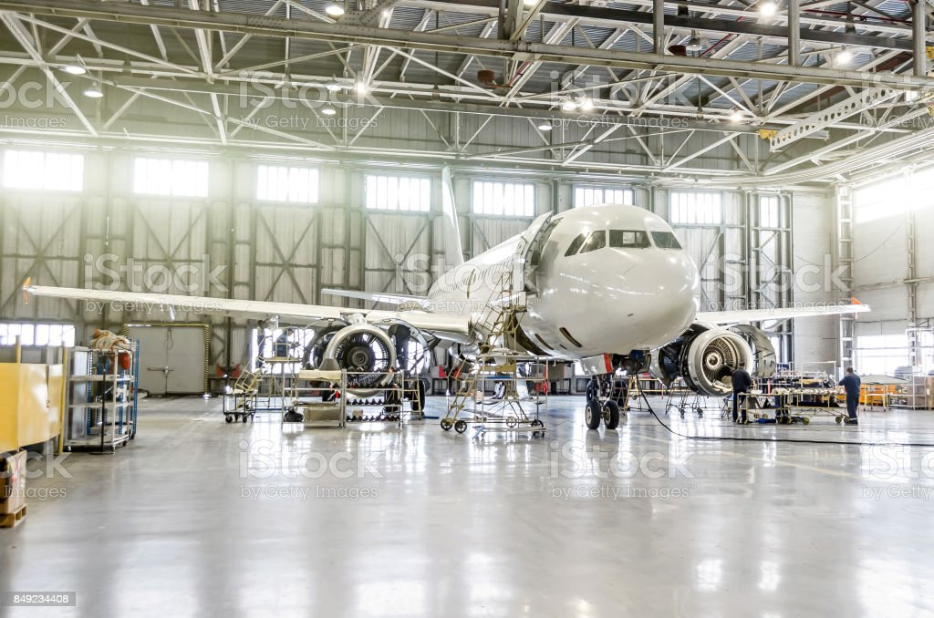 Passenger aircraft on maintenance of engine and fuselage repair in airport hangar stock photo