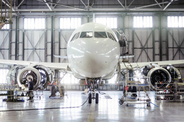Passenger aircraft on maintenance of engine and fuselage repair in airport hangar. stock photo