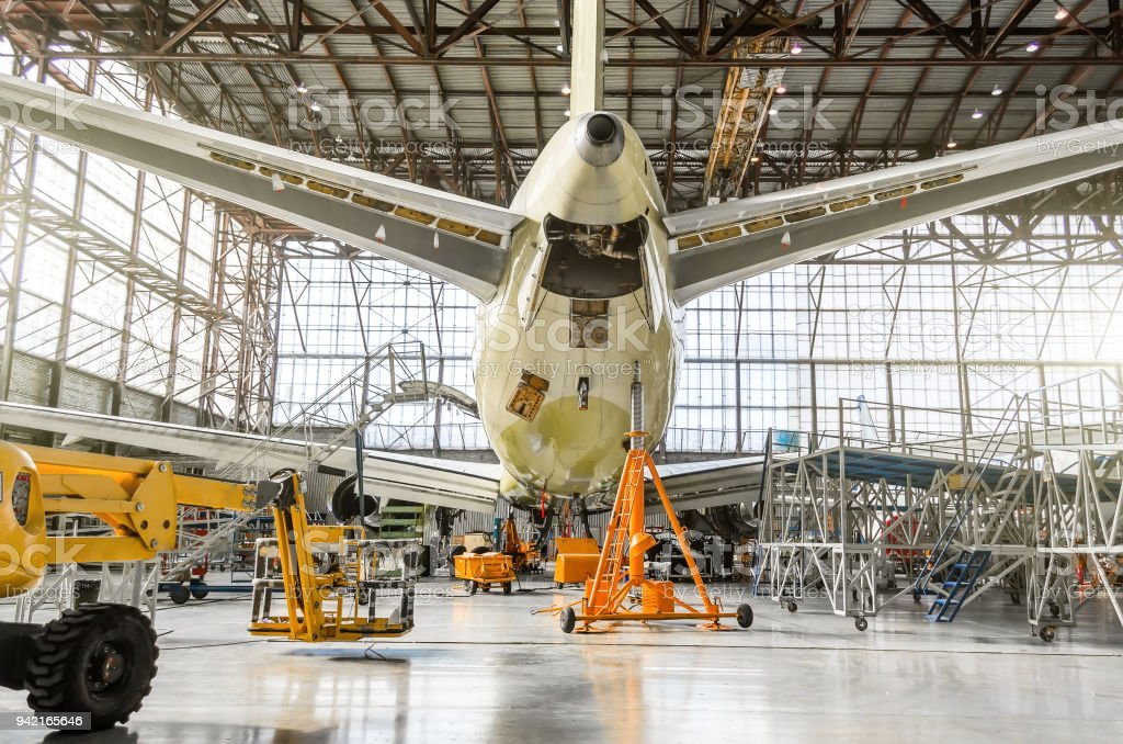 Passenger aircraft on service in an aviation hangar rear view of the tail, on the auxiliary power unit. stock photo