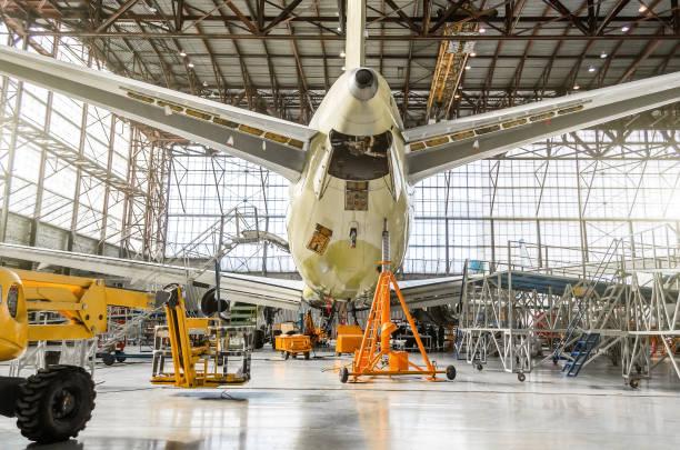 passagiersvliegtuigen over de dienst op een luchtvaart hangar achteraanzicht van de staart, op het hulpaggregaat. - luchtvaartindustrie stockfoto's en -beelden