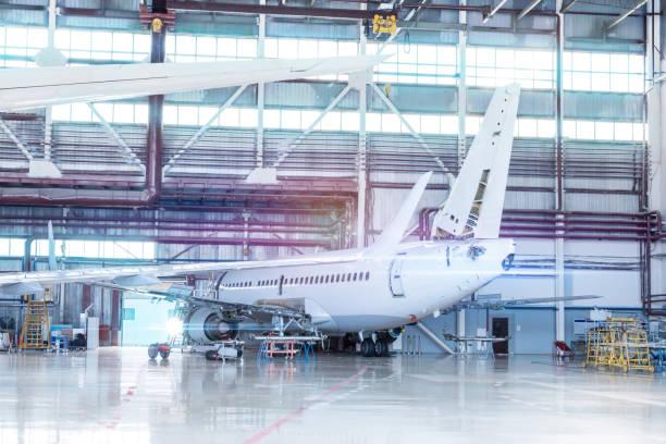 Passagierflugzeuge in Wartung. Überprüfung mechanischer Systeme für den Flugbetrieb. Weißes Düsenflugzeug im Hangar – Foto