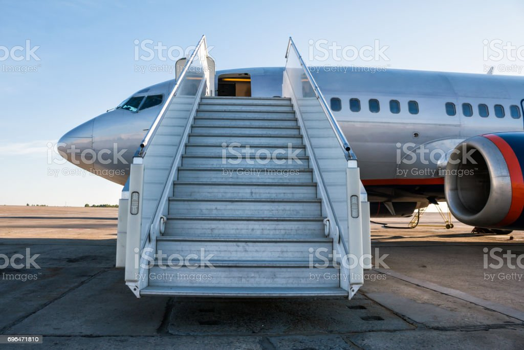 Passenger aircraft with a boarding ramp on the airport apron стоковое фото