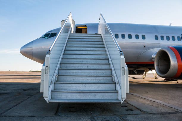 Passenger aircraft with a boarding ramp on the airport apron stock photo