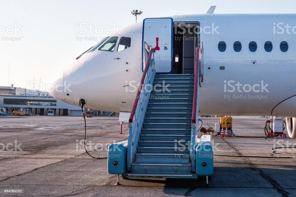 Passenger aircraft with boarding stairs at the airport apron and connected to an external power supply стоковое фото