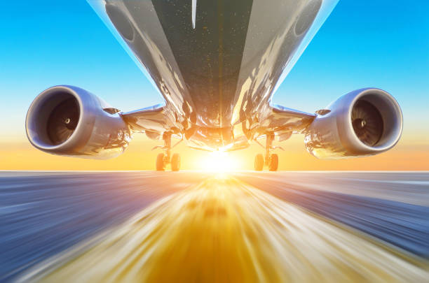 Passenger airplane accelerates at high speed view from below with bright light. stock photo