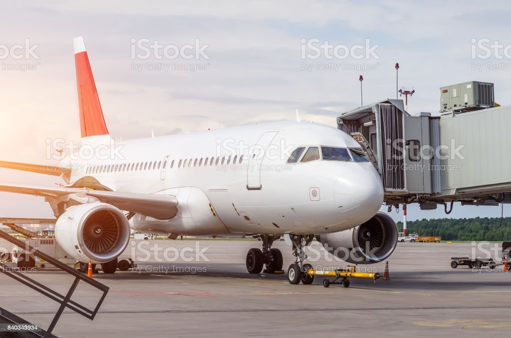 Passenger airplane at the teletrap at the airport, service at the terminal at the time of loading stock photo
