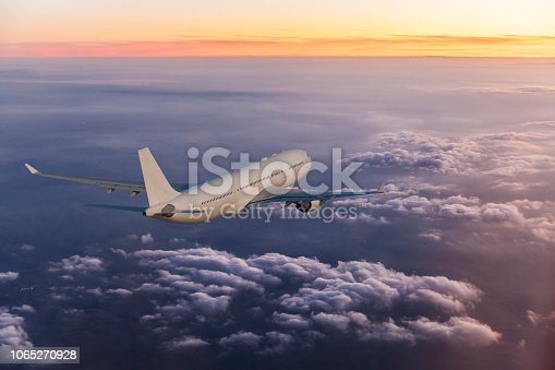 155439315istockphoto Passenger airplane flying above clouds during sunset 1065270928