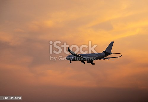 155439315istockphoto Passenger airplane flying above clouds during sunset 1181950920