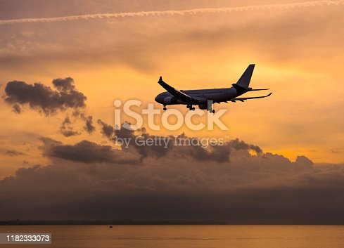 155439315istockphoto Passenger airplane flying above clouds during sunset 1182333073